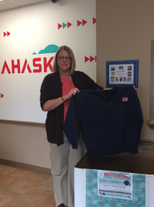 Administrative Assistant, Stacie Luckett displays one of the many jackets that was donated by an employee.